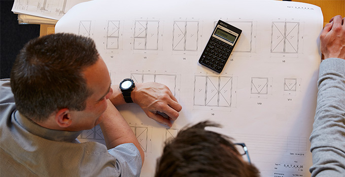 VELFAC employee and customer calculating costs and looking at drawings of new windows